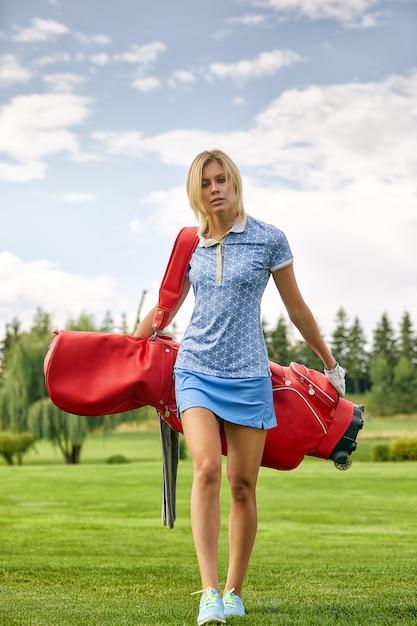 Joueur de golf tenant un équipement de golf sur un champ vert Photo Premium