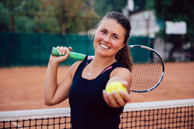 Joueur de tennis. femme active attrayante debout sur le terrain avec une raquette de tennis et une balle Photo gratuit