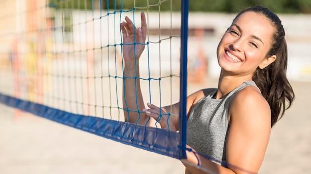 Joueur De Volley-ball Féminin Smiley Sur La Plage Posant Avec Filet Photo gratuit