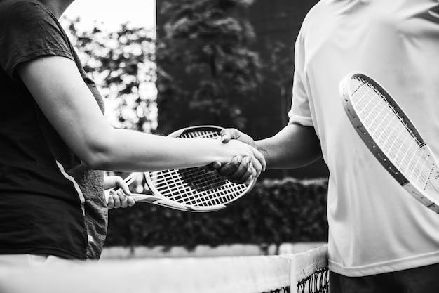 Joueurs se serrant la main après un match de tennis Photo gratuit