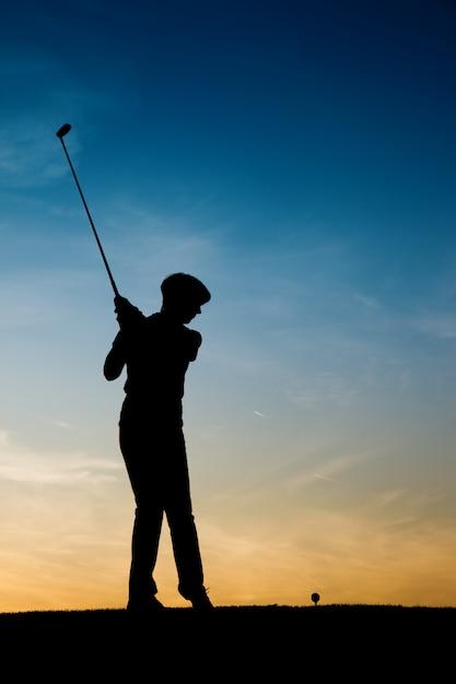 Joueuse de golf senior au coucher du soleil Photo Premium