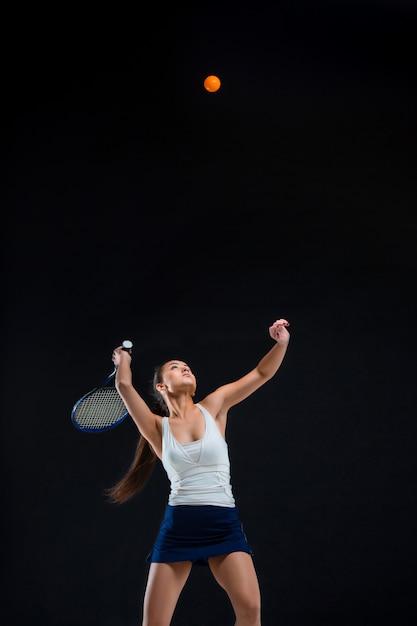 Joueuse De Tennis Belle Fille Avec Une Raquette Sur Fond Sombre Photo gratuit