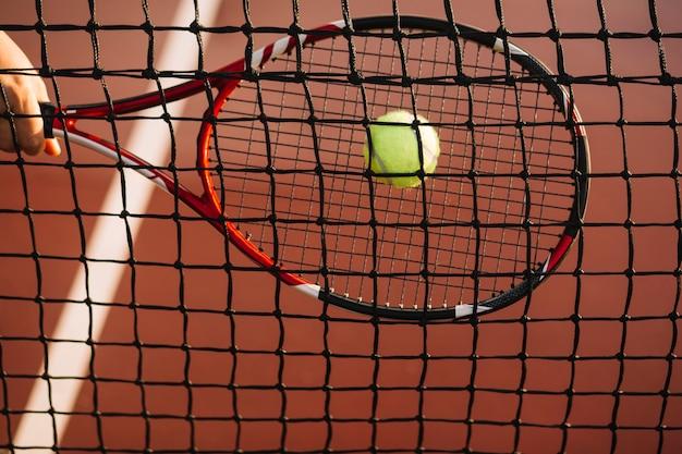 Une joueuse de tennis frappe le ballon dans le filet Photo gratuit