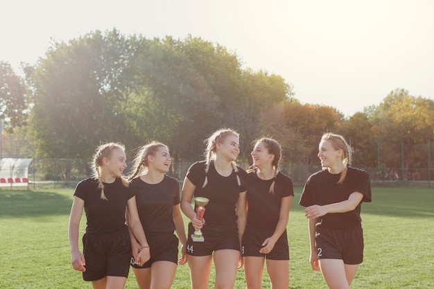 Joueuses de football tenant un trophée Photo gratuit