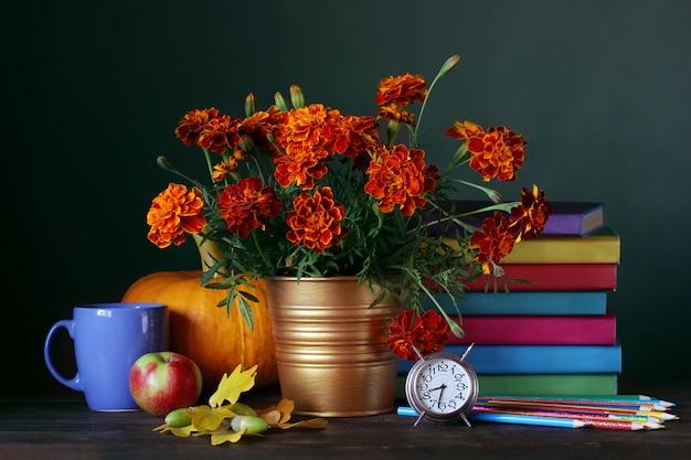 Le jour du professeur. retour à l'école. nature morte avec manuels scolaires, bouquet et fournitures scolaires. Photo Premium
