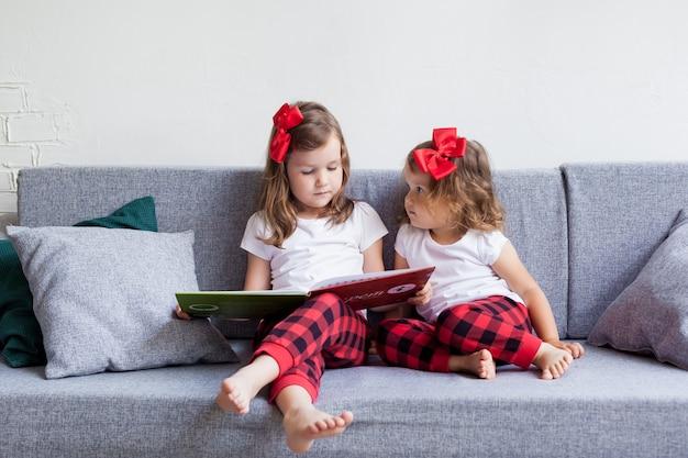 Un jour d'été ensoleillé, deux petites sœurs sont assises sur un canapé et lisent un livre. Photo Premium