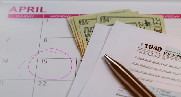 Jour d'impôt, dollars et formulaire 1040 formulaire d'impôt indiquant le jour d'impôt pour le calendrier d'avril avec mots Photo Premium
