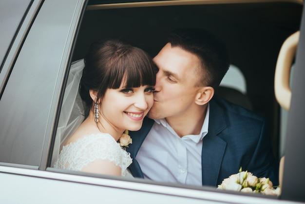 Jour de mariage. baiser de mariage, heureux et beau marié embrasse la mariée dans la voiture de mariage Photo gratuit