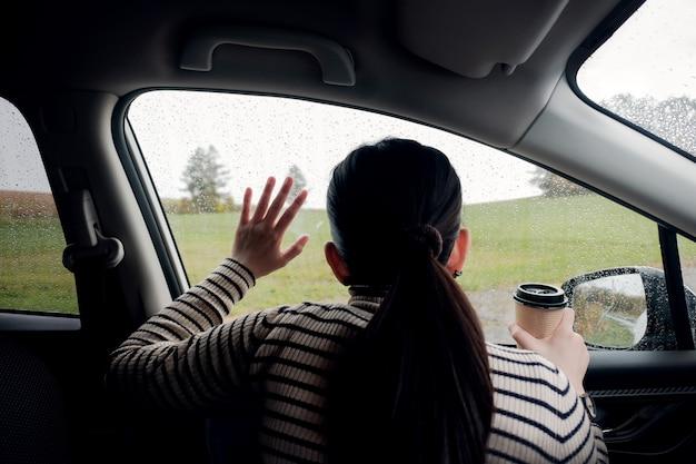 Jour de pluie ou mauvais temps dans un concept de vacances. une femme de tristesse attendant que la pluie cesse Photo Premium