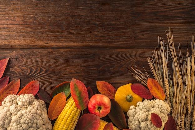Jour De Thanksgiving. Composition Avec Des Légumes Et Des Feuilles De L'automne Sur Un Fond En Bois Foncé Avec Fond Photo Premium