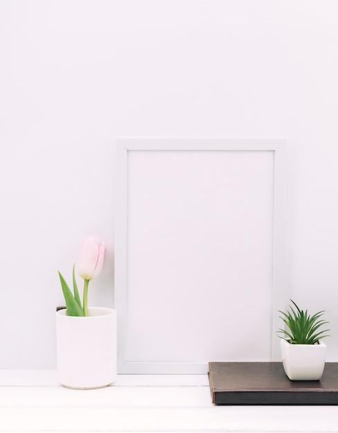 Journal intime; plante; fleur de tulipe avec cadre photo blanc sur tableau blanc Photo gratuit