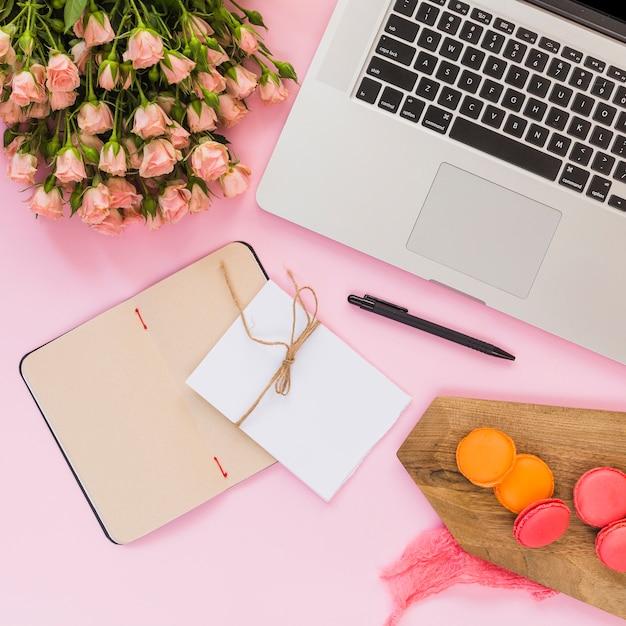 Journal de la page blanche; carte; stylo; bouquet de fleurs; portable; stylo et macarons de planche à découper Photo gratuit