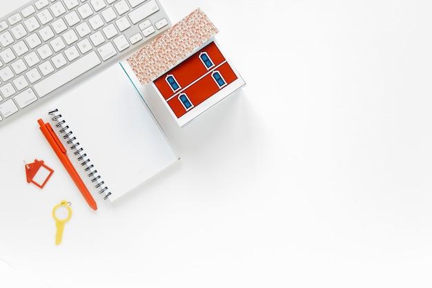 Journal vierge avec modèle de maison miniature et clavier sur fond blanc Photo gratuit