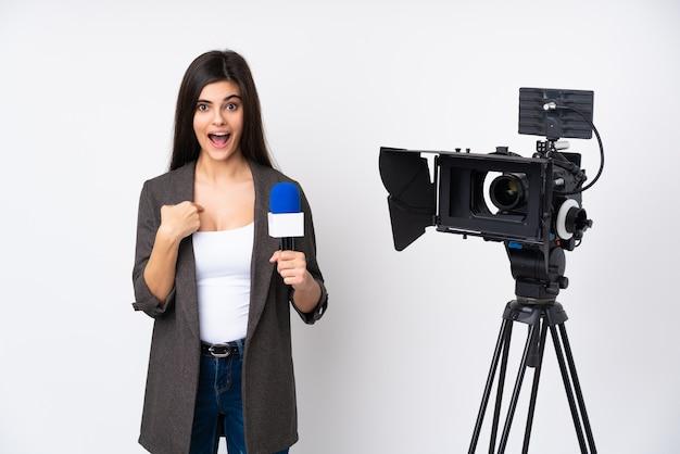 Journaliste Femme Tenant Un Microphone Et Rapportant Des Nouvelles Sur Un Mur Blanc Isolé Avec Une Expression Faciale Surprise Photo Premium