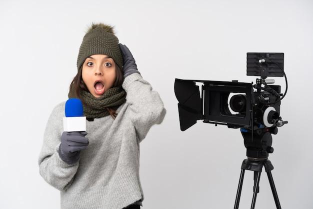 Journaliste Femme Tenant Un Microphone Et Rapportant Des Nouvelles Sur Un Mur Blanc Isolé Avec Expression Surprise Photo Premium