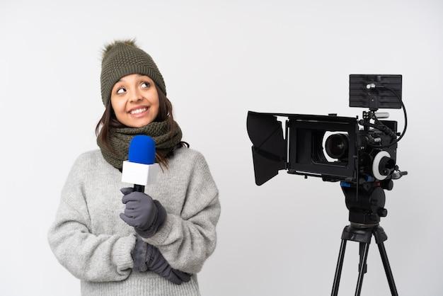 Journaliste Femme Tenant Un Microphone Et Rapportant Des Nouvelles Sur Un Mur Blanc Isolé En Levant Tout En Souriant Photo Premium