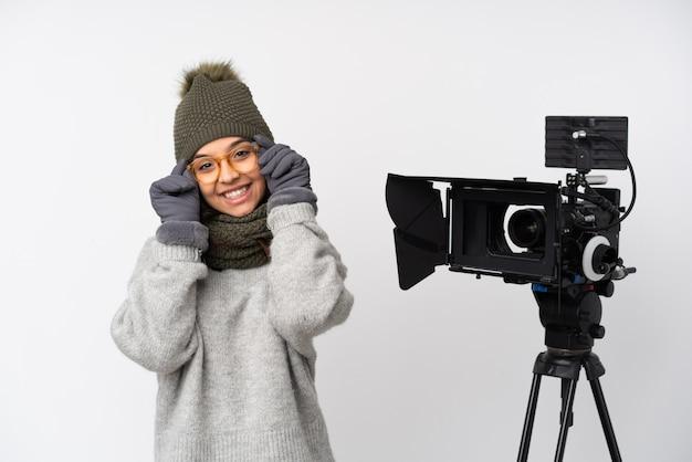 Journaliste Femme Tenant Un Microphone Et Rapportant Des Nouvelles Sur Un Mur Blanc Avec Des Lunettes Et Heureux Photo Premium