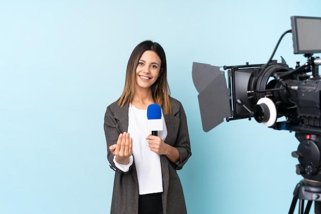 Journaliste Femme Tenant Un Microphone Et Rapportant Des Nouvelles Sur Le Mur Bleu Invitant à Venir Photo Premium