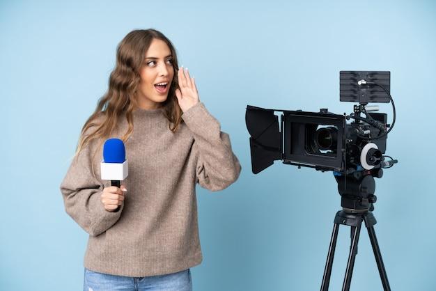 Journaliste Jeune Femme Tenant Un Microphone Et Rapportant Des Nouvelles Criant Avec La Bouche Grande Ouverte Photo Premium