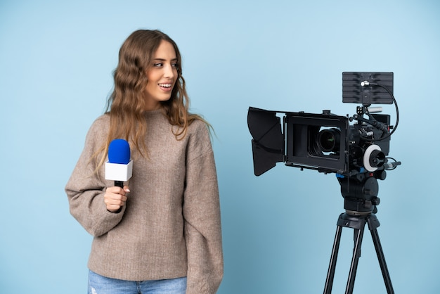 Journaliste Jeune Femme Tenant Un Microphone Et Rapportant Les Nouvelles à La Recherche De Côté Photo Premium