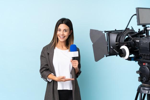 Journaliste Tenant Un Microphone Et Rapportant Des Nouvelles Tendant La Main Sur Le Côté Pour Avoir Invité à Venir Photo Premium