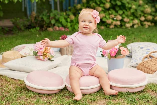 Journée Des Enfants, Une Fille Dans Le Parc Est Assise Dans Un Panier Avec Des Macarons Sur Un Pique-nique Estival Photo Premium