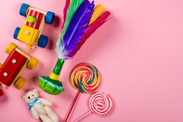 La journée des enfants. train en bois, volant, ours en peluche, sucettes sur fond néon rose Photo Premium