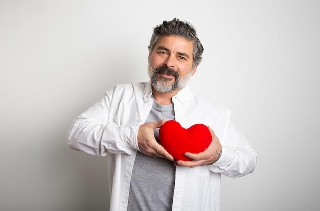 Journée Mondiale Du Coeur Fond Blanc Homme Tenant Un Coeur Rouge. Joyeuse Saint Valentin Photo Premium