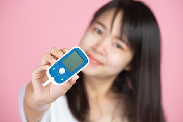 Journée Mondiale Du Diabète; Woman Holding Glucomètre Sur Mur Rose Photo gratuit
