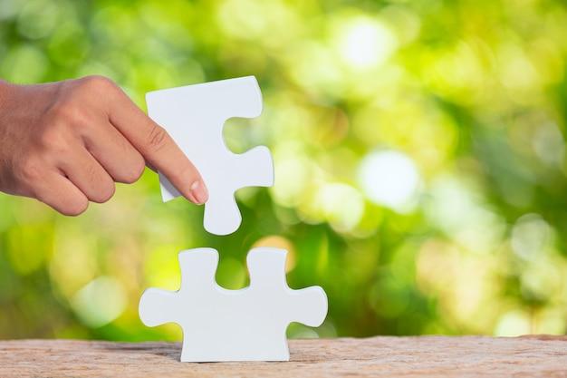 Journée Mondiale De L'habitat, Gros Plan Photo D'un Morceau De Puzzle Blanc à La Main Photo gratuit