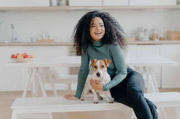 Joyeuse Afro Femme Assise Sur Un Banc Blanc Avec Chien Photo Premium