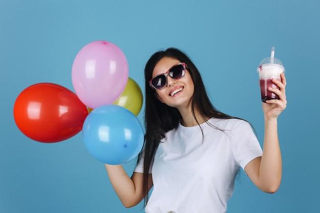 Joyeuse brune en lunettes de soleil noires semble heureux posant avec un cocktail et des ballons Photo gratuit