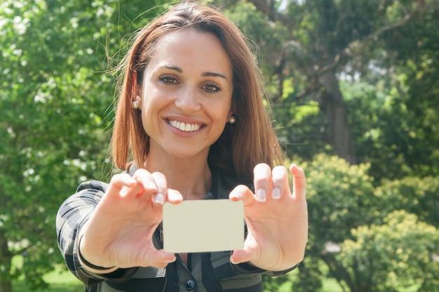 Joyeuse clientèle féminine détenant une carte de visite Photo gratuit