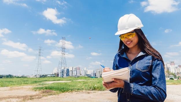 Joyeuse dame afro-américaine dans un casque de sécurité, prenant des notes près de la ligne haute tension Photo gratuit