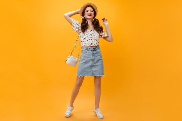 Joyeuse Dame Vêtue D'une Jupe En Jean Et D'un Haut Court Posant Avec Un Sac Blanc Sur Fond Orange. Photo gratuit