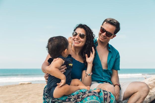 Joyeuse famille assise sur la plage Photo gratuit