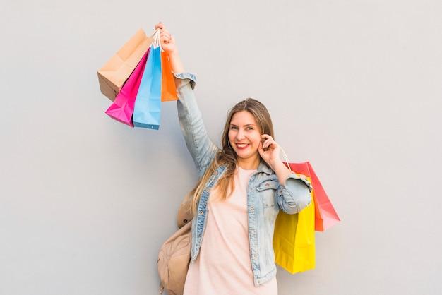 Joyeuse femme debout avec des sacs brillants au mur Photo gratuit
