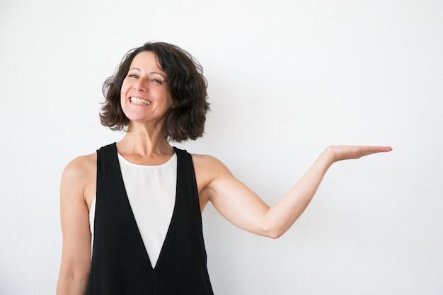 Joyeuse femme excitée en présentant des informations occasionnels Photo gratuit