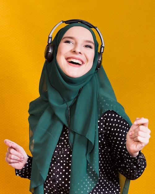 Joyeuse femme islamique, appréciant la musique sur fond jaune Photo gratuit