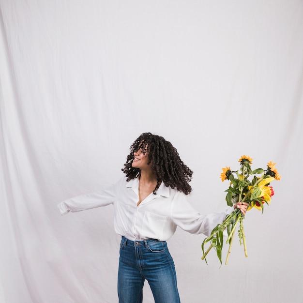 Joyeuse Femme Noire Tenant Un Bouquet De Fleurs Photo gratuit
