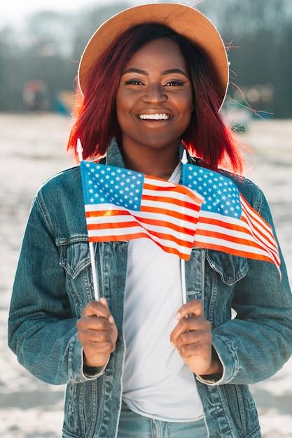 Joyeuse femme noire tenant des petits drapeaux américains Photo gratuit