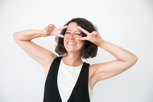 Joyeuse femme qui rit en geste de paix décontracté Photo gratuit