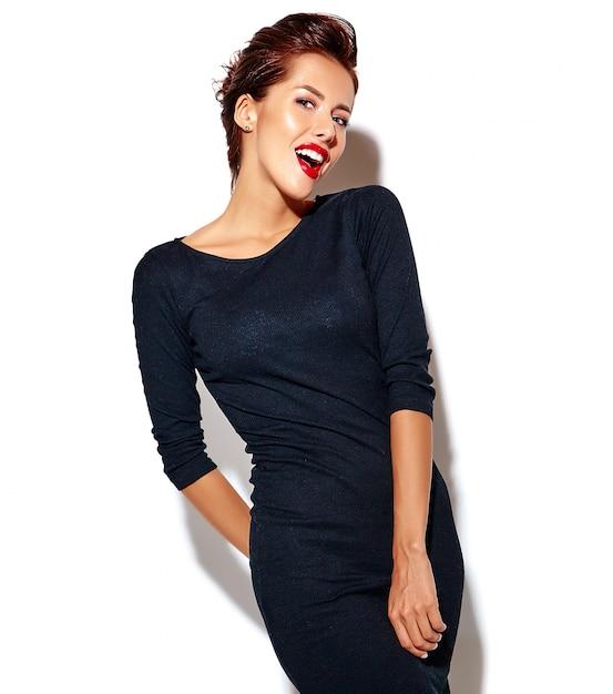 Joyeuse Femme Souriante De Mode De Clin De œil Devient Fou Dans Des Vêtements Noirs Décontractés Avec Des Lèvres Rouges Sur Le Mur Blanc Photo gratuit