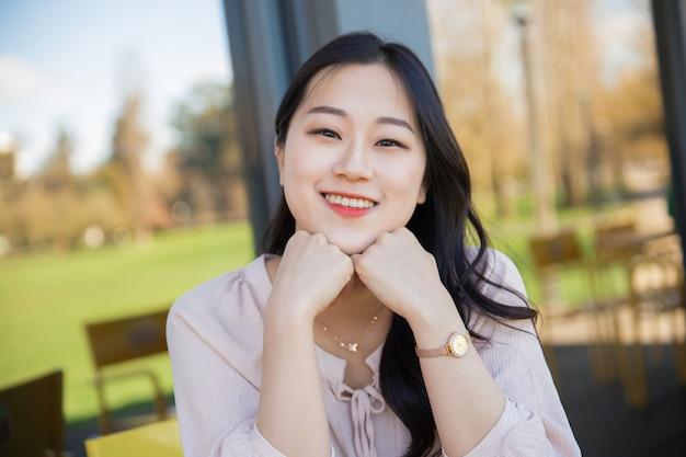 Joyeuse femme touriste asiatique se détendre sur la terrasse de l'hôtel Photo gratuit