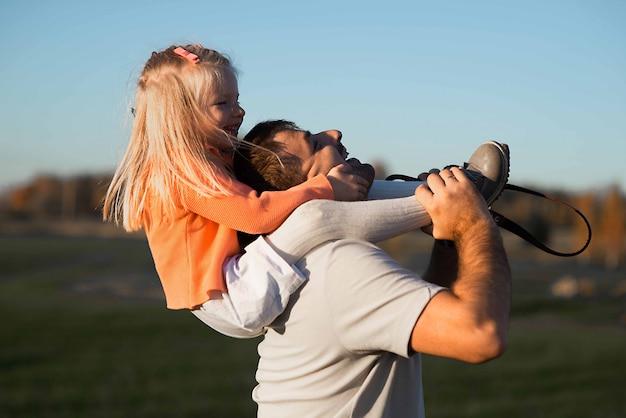 Joyeuse fête des pères! enfant fille et papa jouant sur la nature dans le champ de l'été Photo Premium