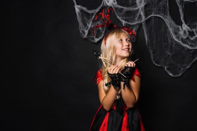 Joyeuse fille en costume rouge avec des jouets d'halloween Photo gratuit