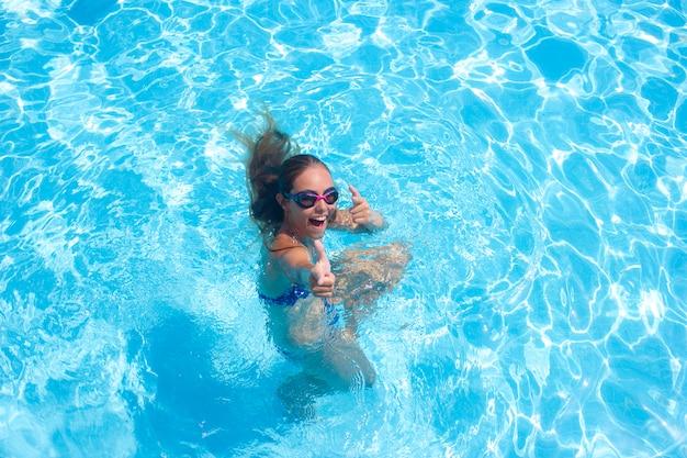 Joyeuse fille dans la piscine en souriant et en montrant les pouces vers le haut Photo Premium
