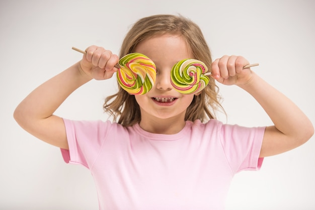 Joyeuse fille qui couvre les yeux avec des sucettes et souriant. Photo Premium
