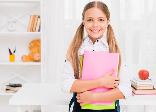 Joyeuse fille souriante avec des livres Photo gratuit