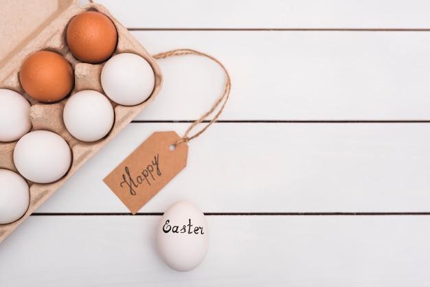 Joyeuse Inscription De Pâques Avec Des Oeufs Dans Un Rack Photo gratuit